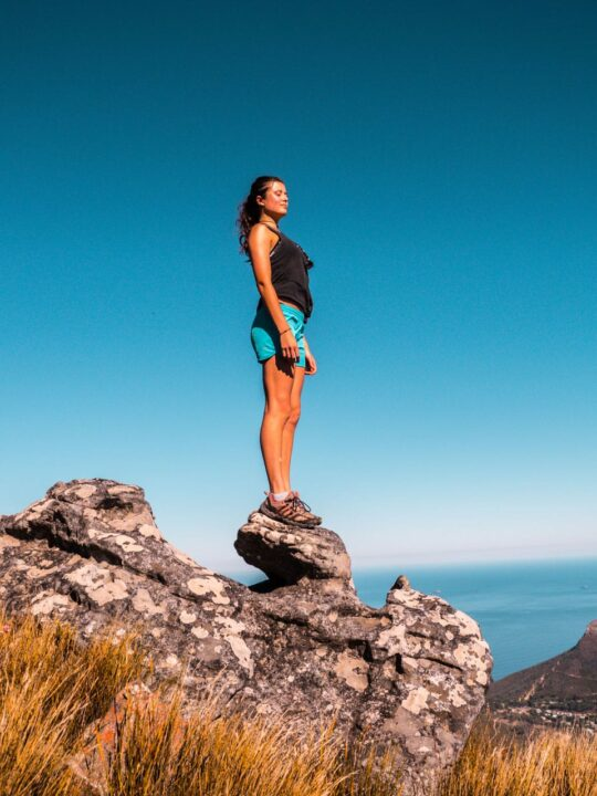 Girl in hiking shorts taking in the view from a mountain top near Cape Town